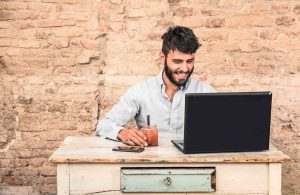Young hipster guy with mustache sitting at vintage desk with laptop computer in grunge alternative office - Concept of start up business enjoying working hours - Soft retro desaturated filtered look